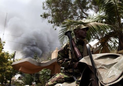 A soldier  holds a RPG near the Westgate shopping mall in Nairobi, Kenya, as smoke rises from it / AP