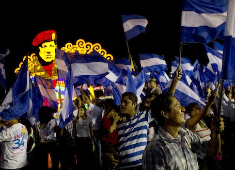 Sandinista supporters hold Nicaraguan flags in ceremony honoring Hugo Chavez in Managua, Nicaragua / AP