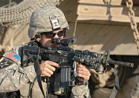 An infantryman of the 3rd US Stryker Brigade Combat Team aims with this M4A1 carbine during a search operation in Bagdad, Iraq, March 2007