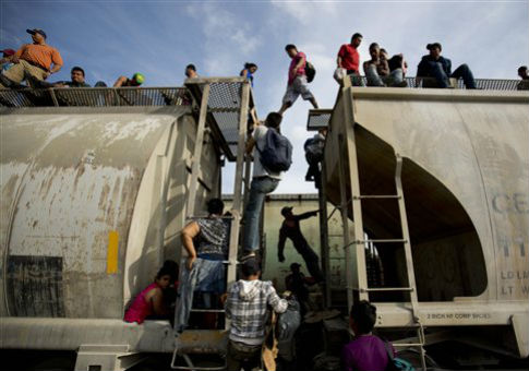 Central American migrants climb on a north bound train during their journey toward the U.S.-Mexico border / AP