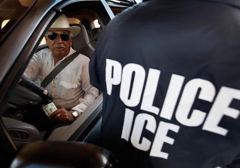 A special agent from Immigration and Customs Enforcement (ICE) searches a vehicle heading into Mexico
