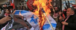 Palestinian protestors burn the Israeli flag and a poster of President Donald Trump