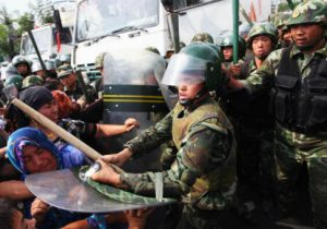 Chinese policemen push Uighur women protesting in Urumqi, capital of Xinjiang region in China